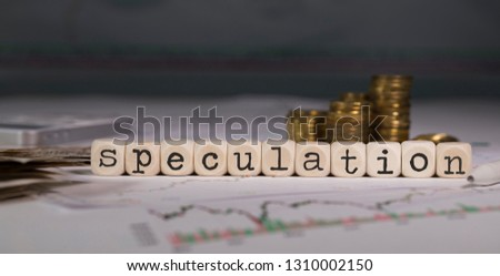 Word SPECULATION composed of wooden letter. Stacks of coins in the background. Closeup
