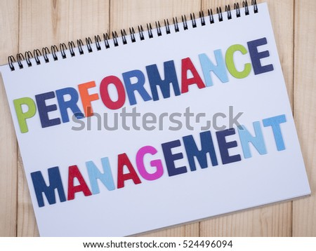 Word spelling Performance Management on white notebook with wood background, top view #524496094