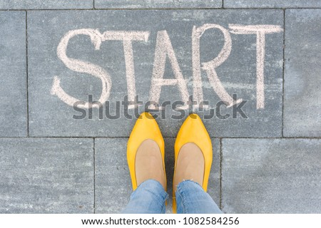 Word start on the asphalt and feet woman