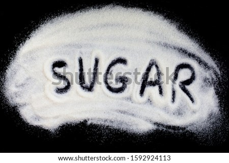 Word sugar hand lettering on a placer of refined white sugar. Beet sugar crystals granules on a black background