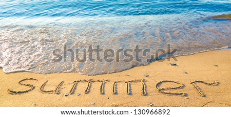 word summer written on wet sand by the sea