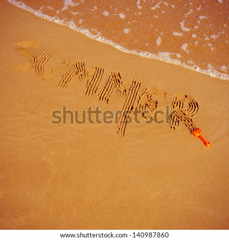 word summer written with a toy rake in the sand, on the seashore