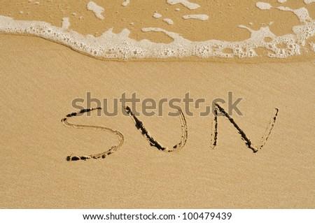 word sun written on the sand of a beach