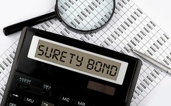 Word SURETY BOND on calculator. Business and tax concept.