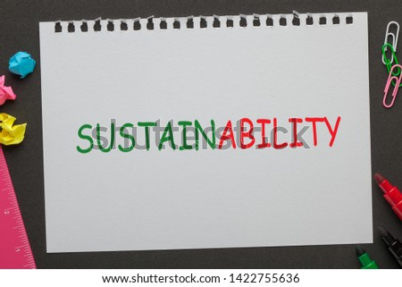 Word Sustainability on notebook paper and office supplies on black background. #1422755636