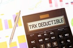 Word TAX DEDUCTIBLE on calculator. Business and tax concept