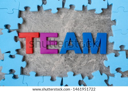 Word TEAM in a middle of jigsaw puzzle frame.Business concept, teamwork concept