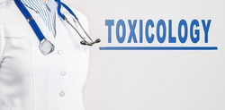 Word - Toxicology on a white background. Nearby is a doctor in white coat and stethoscope. Medical concept
