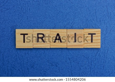 word trait made of brown wooden letters on a blue table