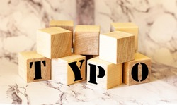 Word typo of wooden blocks on a marble table