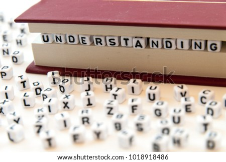 Word understanding written with letters between a book pages white background with letters spread around education reading concept photo
