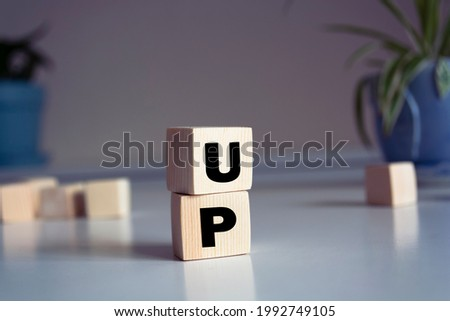 Word UP made from wooden letters on pink background. Concept of growth