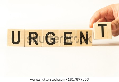 Word urgent. Wooden small cubes with letters isolated on white background with copy space available.Business Concept image. Stockfoto ©
