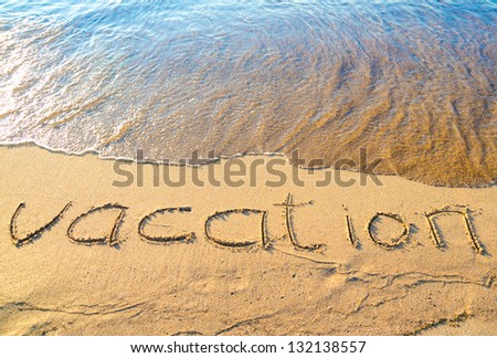 "word ""vacation"" written on wet sand by the sea"