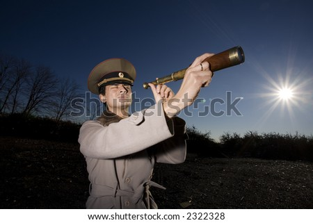 Word War II: suspicious russian soldier looking for enemies using a spyglass