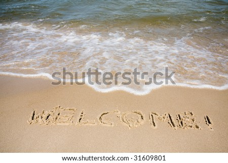 Word welcome written in a sandy tropical beach