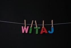Word Witaj on black background. Witaj means hello in Polish.