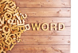 Word word made with block wooden letters next to a pile of other letters over the wooden board surface composition