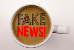 Word, writing Fake News text in coffee in cup. Business concept for Propaganda Newspaper Fake News on white background with space. Black text with red word.