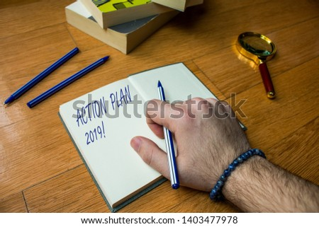 Word writing text Action Plan 2019. Business concept for proposed strategy or course of actions for current year Close up view man writing notebook pen set lying wooden table two books. #1403477978