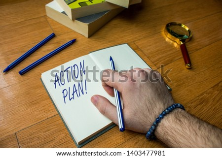 Word writing text Action Plan. Business concept for proposed strategy or course of actions for certain time Close up view man writing notebook pen set lying wooden table two books. #1403477981