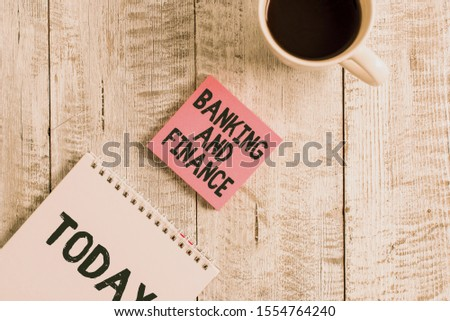 Word writing text Banking And Finance. Business concept for Accounting and entities stocks Money interests Stationary placed next to a cup of black coffee above the wooden table.
