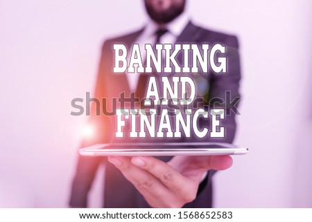 Word writing text Banking And Finance. Business concept for Accounting and entities stocks Money interests Male human wear formal work suit hold smart hi tech smartphone use one hand.