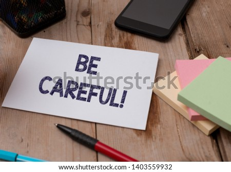 Word writing text Be Careful. Business concept for making sure of avoiding potential danger mishap or harm Top view wooden table stationary paper tablet pen colored stick pad notes. #1403559932