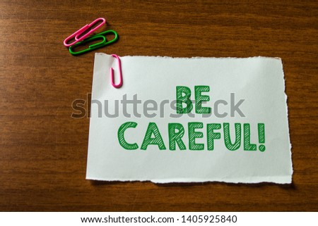 Word writing text Be Careful. Business concept for making sure of avoiding potential danger mishap or harm Close up blank stationary paper hold three colored clips lying wooden table. #1405925840