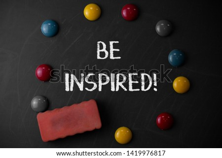 Word writing text Be Inspired. Business concept for fill someone with urge or ability to do or feel something Round Flat shape stones with one eraser stick to old chalk black board.