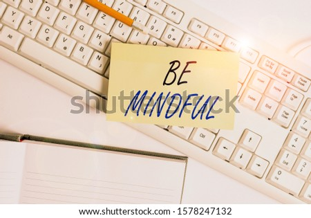 Word writing text Be Mindful. Business concept for paying close attention to or being conscious of something White pc keyboard with empty note paper and paper clips above white background. #1578247132