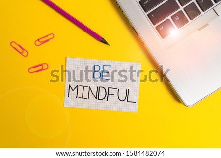 Word writing text Be Mindful. Business concept for paying close attention to or being conscious of something Trendy metallic laptop clips pencil squared paper sheet colored background.