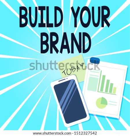 Word writing text Build Your Brand. Business concept for enhancing brand equity using advertising campaigns Layout Smartphone Off Sticky Notes Clipboard with Pie Chart and Bar Graph.