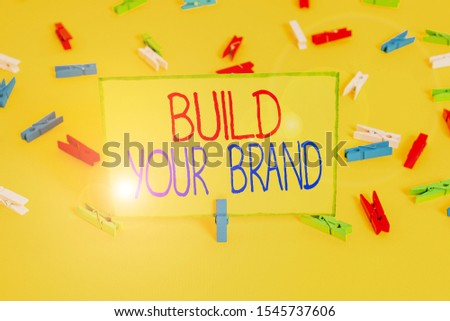Word writing text Build Your Brand. Business concept for enhancing brand equity using advertising campaigns Colored clothespin papers empty reminder yellow floor background office.