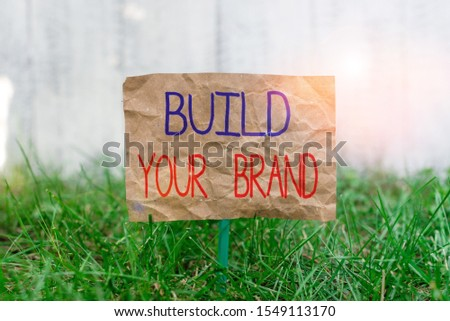 Word writing text Build Your Brand. Business concept for enhancing brand equity using advertising campaigns Crumpled paper attached to a stick and placed in the green grassy land.