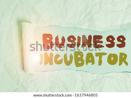 Word writing text Business Incubator. Business concept for company that helps new and startup companies to develop Cardboard which is torn in the middle placed above a plain table backdrop.