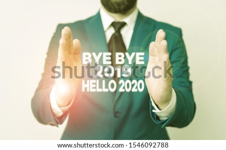 Word writing text Bye Bye 2019 Hello 2020. Business concept for saying goodbye to last year and welcoming another good one Man with opened hands in fron of the table. Mobile phone and notes on the Stockfoto ©