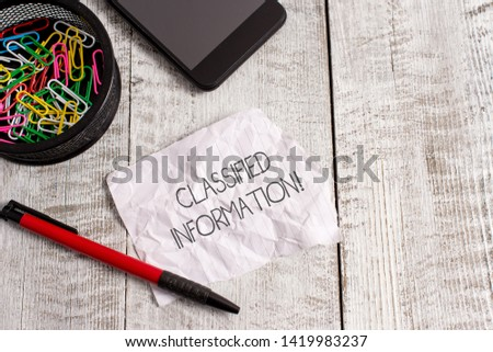 Word writing text Classified Information. Business concept for Sensitive Data Top Secret Unauthorized Disclosure Wrinkle paper and notebook plus stationary placed above wooden background.