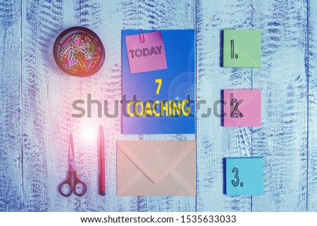 Word writing text 7 Coaching. Business concept for Refers to a number of figures regarding business to be succesful Envelope letter sticky note ballpoint clips can scissors wooden background.