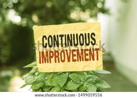 Word writing text Continuous Improvement. Business concept for ongoing effort to improve products or processes Plain empty paper attached to a stick and placed in the green leafy plants.