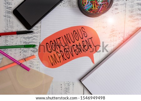 Word writing text Continuous Improvement. Business concept for ongoing effort to improve products or processes Smartphone pens envelope clips speech bubble sheet notebook wooden back.