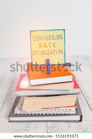 Word writing text Conversion Rate Optimization. Business concept for system for increasing percentage of visitors pile stacked books notebook pin clothespin colored reminder white wooden.