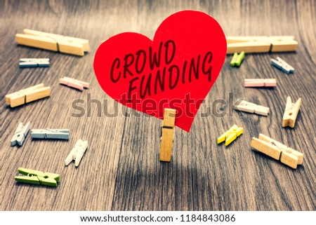 Word writing text Crowd Funding. Business concept for Fundraising Kickstarter Startup Pledge Platform Donations Clothespin holding red paper heart several clothespins wooden floor romance. #1184843086