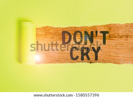 Word writing text Don T Cry. Business concept for Shed tears typically as an expression of distress pain or sorrow Cardboard which is torn in the middle placed above a wooden classic table. #1580557396