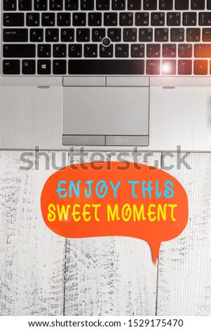 Word writing text Enjoy This Sweet Moment. Business concept for encouraging someone to love his life timeline Close view open laptop blank speech bubble downwards lying vintage table.