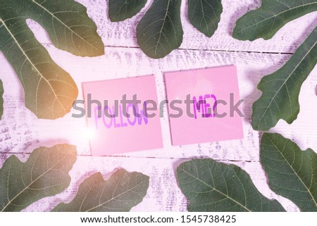 Word writing text Follow Me Question. Business concept for go or come after demonstrating or thing proceeding ahead Leaves surrounding notepaper above a classic wooden table as the background. #1545738425
