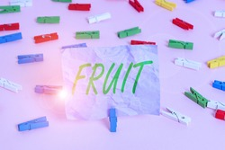 Word writing text Fruit. Business concept for sweet and fleshy product of a tree or other plant that contains seed Colored clothespin papers empty reminder pink floor background office pin.