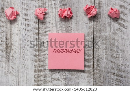 Word writing text Fundraising. Business concept for seeking to generate financial support for charity or cause Thick set of plain note paper with scraps on the wooden textured table. #1405612823