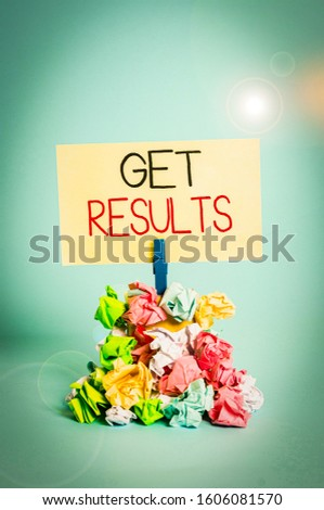 Word writing text Get Results. Business concept for to proceed or arise as a consequence effect or conclusion Reminder pile colored crumpled paper clothespin reminder blue background.