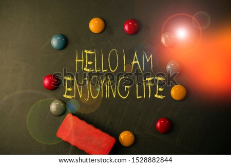 Word writing text Hello I Am Enjoying Life. Business concept for Happy relaxed lifestyle Enjoy simple things Round Flat shape stones with one eraser stick to old chalk black board. #1528882844
